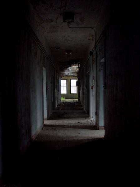 dark hall photo of the abandoned foxboro state hospital